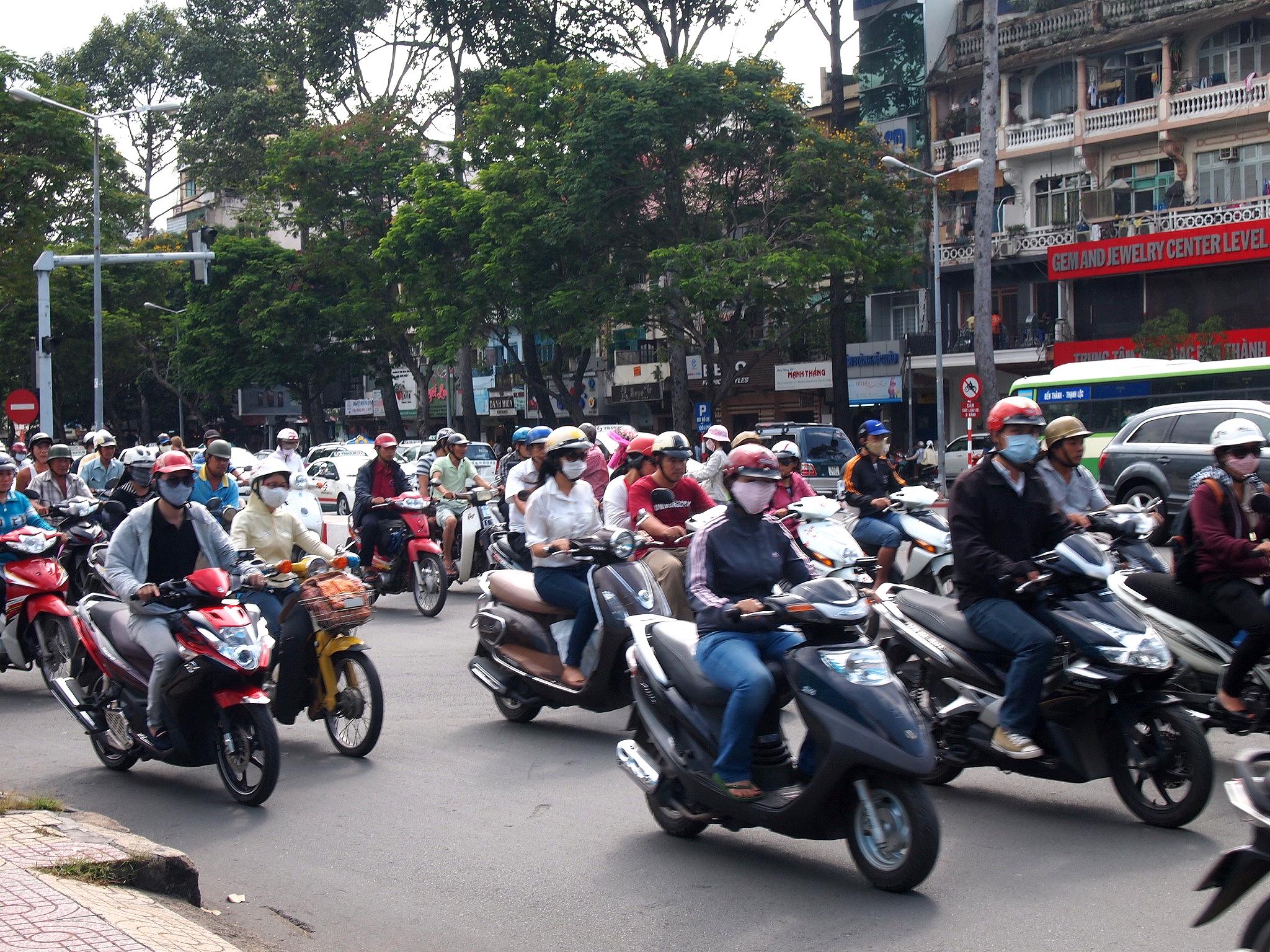 ベトナムの街中にはバイクがあふれ、排気ガスのためマスクをしている。