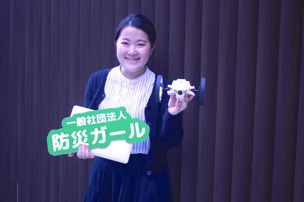 田中美咲さん(一般社団法人防災ガール 代表理事)。看板とパソコンと、災害時に役立つように研究中のドローンを手に。